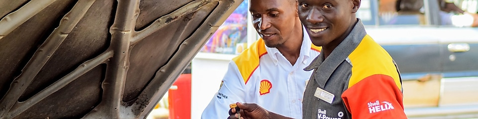 An enginner pours Shell lubricant into a car engine